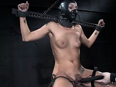 Sara Faye locked in steel bondage cage with rubber hood play.